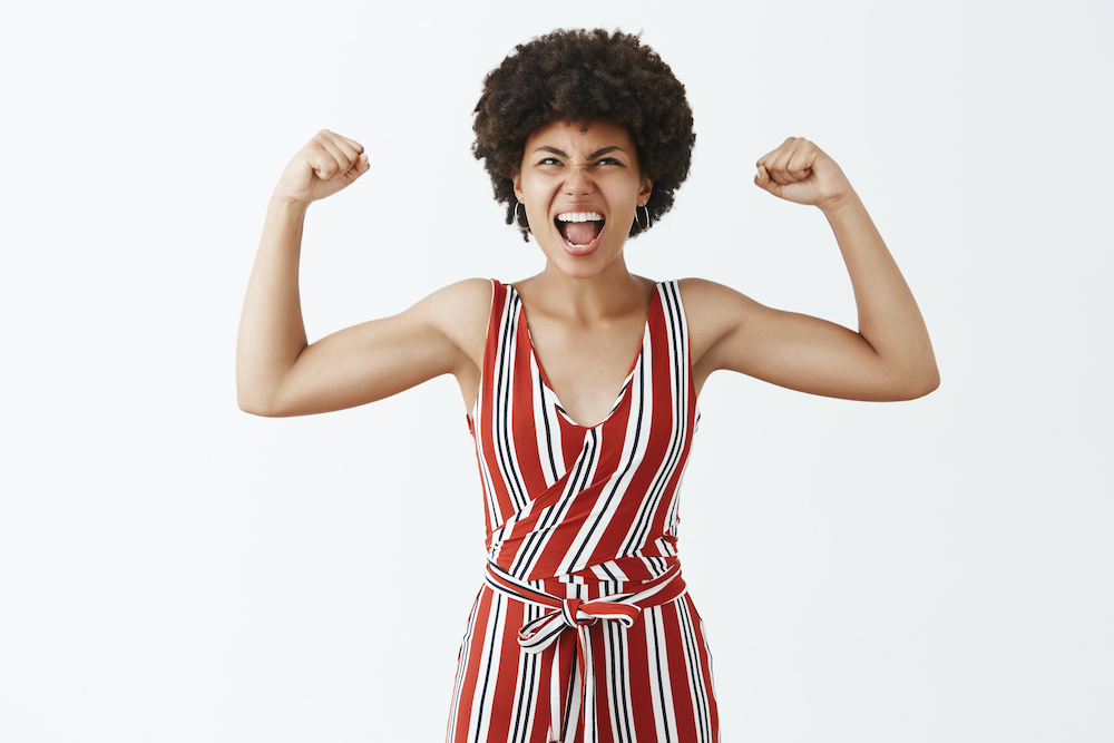 portrait-triumphing-joyful-expressive-good-looking-african-american-sportswoman-stylish-striped-overalls-raising-arms-show-muscles-shouting-from-joy-looking-up.jpg